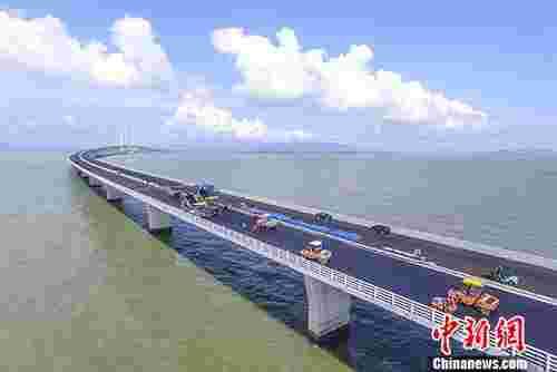 历时8年多的建设,目前港珠澳大桥进入收官阶段,大桥交通工程正在有条不紊地推进着,桥面铺装也将在6月底全面完工,港珠澳大桥具备年内全线通车条件。图为6月8日,工人们在港珠澳大桥上进行桥面铺装。 中新社记者 陈骥F 摄