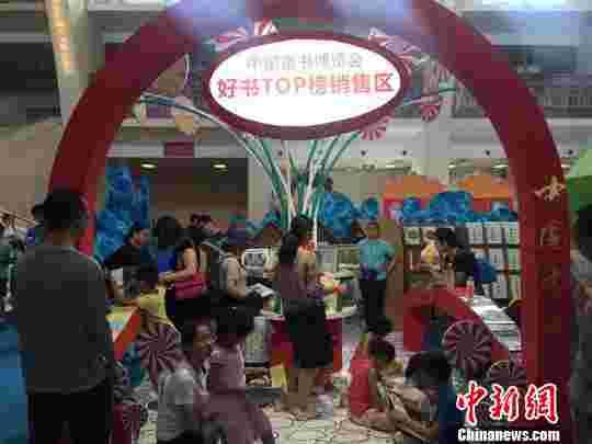"""7月9日,""""童阅同享 智造未来""""2017年中国童书博览会高峰论坛在京召开。图为博览会现场设置的好书TOP榜销售区,小朋友们在这里阅读并挑选书籍。(完) 尹力 摄"""